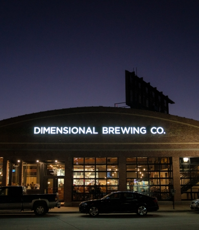 Close-up photo of someone holding a beer at Dimensional Brewing in Dubuque Iowa
