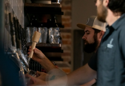 Bartenders pouring beers at Dimensional Brewery in downtown Dubuque, Iowa